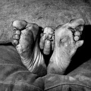© Roger Ballen, Puppy between feet